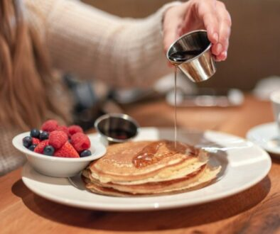 meeting-friends-for-breakfast-young-woman-pouring-warm-maple-syrup-on-pancakes_t20_pR7238